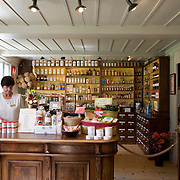 Woman behind counter in the Handicraft workers house with a historical pharmacy, from Herzogenbuchsee BE circa 1778, re-located to the Ballenberg Historical Open-Air Museum, Ballenberg, Switzerland<br />