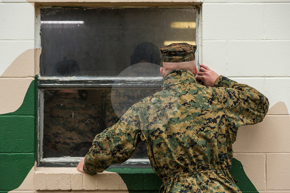 US Marine Drill Instructors peak though the windows of the gas chamber watching recruits during bootcamp January 13, 2014 in Parris Island, SC.
