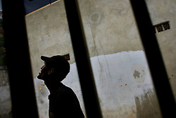 A member of the Venezuelan MilitaryReserve stands outside a home in Coche, a poor slum in Caracas.