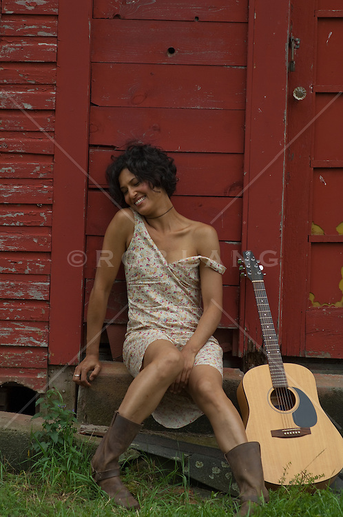 African american woman sitting on a step with her guitar beside her