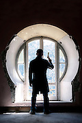a man with a gun in front of an old window in an abandoned building
