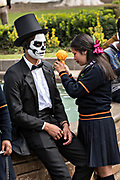 A young girl adds a marigold flower to the Dapper Skeleton costume of her brother for the Day of the Dead or Día de Muertos festival October 31, 2017 in Patzcuaro, Michoacan, Mexico. The festival has been celebrated since the Aztec empire celebrates ancestors and deceased loved ones.