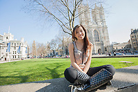 Full length portrait of young woman sitting against Westminster Abbey in London; England; UK
