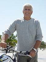 Smiled senior man on bicycle on tropical beach