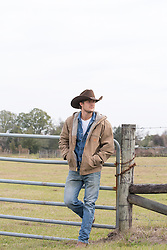 rugged All American cowboy leaning on a fence