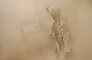 IRAQ, BAGHDAD - JUNE 28: A soldier attached to Alpha Company, 4th Battalion, 6th Armoured, 4th Brigade, 3rd Infantry Division is caught in a cloud of dust as a patrol returns to the combat outpost in the suburb of Sadiyah, June 28, 2008 in Baghdad, Iraq. Neighbourhoods like Sadiyah became a battleground for Shiite militias and Sunni extremists after the bombing of the Golden Mosque in Samarra in 2006. Tens of thousands of people were either forced out of their homes or fled the violence to neigbouring countries or other parts of Iraq. Now predominantly Shiite, Sadiyah is being used as a test case by the Iraqi government to encourage the millions who have fled - many of which have the skills and money to rebuild the country. Since early 2008, Iraq's security situation has improved with oil production is increasing, record government surplus and easing sectarian tensions. (Photo by Warrick Page)