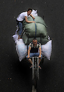 GUANGZHOU, CHINA - JUNE 04: (CHINA OUT) <br /> <br /> Life On The Tricycle<br /> <br /> A porter rides a tricycle carrying cloths and people at Guangzhou International Textile City on June 3, 2014 in Guangzhou, Guangdong Province of China. More than 1,500 tricycles are active in the business district.  <br /> ©Exclusivepix
