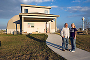 "Greensburg, Kansas, USA..Scott Eller and his daughter Stacey in front of their house, 'The Eller Home'..The building is energy efficient and more tornado resistant than conventional homes. Eller's gas bill went from $200 a month to only $30...""Greensburg: Better, Stronger, Greener!"".On May 4, 2007, an EF5 tornado cut a 1.7-mile path of destruction through Greensburg, Kansas. Winds reaching speeds of 205 miles per hour uprooted trees, demolished homes and leveled the town. Eleven people died and 95% of the buildings were destroyed beyond repair. Residents have since worked furiously to rebuild it in a way that is both economically and environmentally sustainable and to meet the highest environmental standards. Greensburg, whose population has dropped from about 1400 to 800 following the storm and is now growing again, is currently the greenest town in America and the first in the United States to pass a resolution to certify that all city-owned buildings earn LEED Platinum accreditation, the highest level of the LEED rating system...Foto © Stefan Falke"