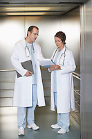 Physicians Discussing Chart in hospital Elevator