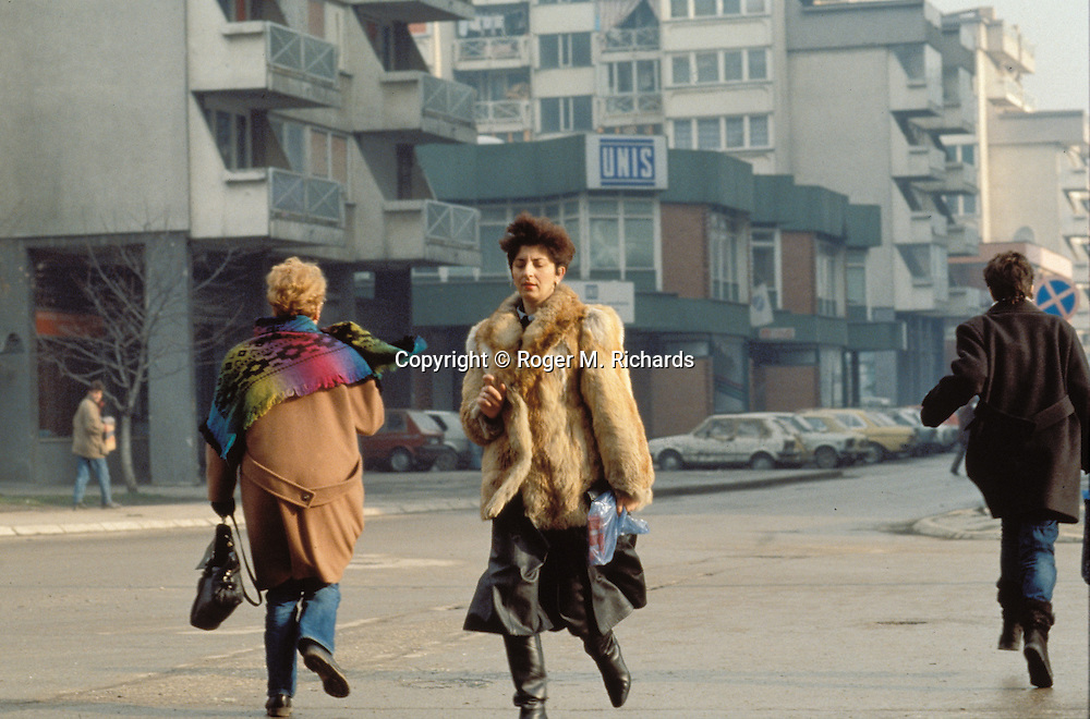 Women run from a Bosnian Serb sniper firing a high-rise building from the suburb of Grbavica into Sarajevo, 1992. (Photo by Roger Richards)