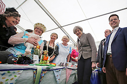 © Licensed to London News Pictures. 13/05/2017. Lisburn, UK. British prime minister THERESA MAY greets a group of woman in costume, during a visit to Balmoral Show at Balmoral Park in Lisburn, Northern Ireland, while campaigning ahead of a general election which takes place on June 8, 2017.  Photo credit: Kalista McErlane/LNP