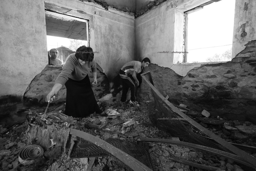Georgian refugees returning to their burnt out house in Ergneti, located in the so called bufferzone between Gori and Tskhinvali, few days after the withdrawal of the russian forces from the area. The bufferzone was etablished after a short war in August 2008 as the georgian army assulted South Ossetia to overthrow the local separatist government.
