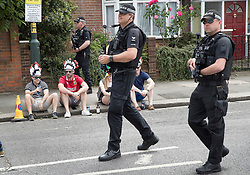 © Licensed to London News Pictures. 27/05/2017. London, UK. Exeter Chiefs rugby fans watch as an armed police patrol passes them outside Twickenham stadium ahead of the Aviva Premiership Rugby Final. Security has been increased at venues across the UK, with the military called in to help police, following a terrorist attack at a music concert in Manchester on Monday evening. Photo credit: Peter Macdiarmid/LNP