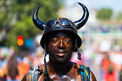 """A man is smeared in oil from """"Jouvert"""" which takes place in the early morning as day one, Children's Day, of the Notting Hill Carnival gets underway in London. London, August 25 2019."""