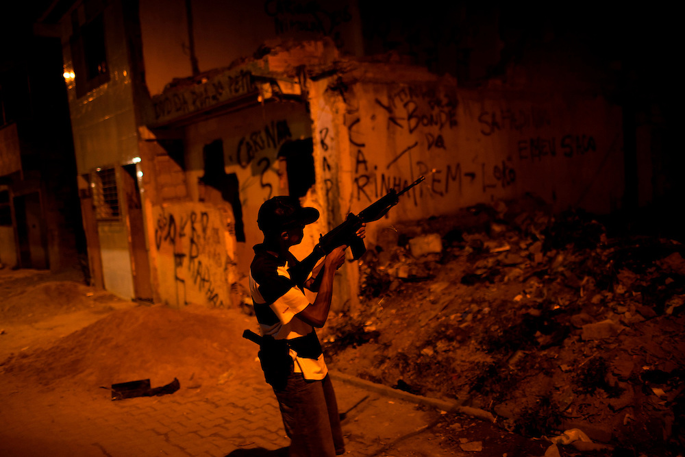 In this Aug. 11, 2012 photo, a trafficker test fires a riffle in the Mandela slum in Rio de Janeiro, Brazil. <br /> <br />  The South American country began experiencing a public health emergency in recent years as demand for crack boomed and open-air &quot;cracolandias,&quot; or crack lands, popped up in the sprawling urban centers of Rio and Sao Paulo, with hundreds of users gathering to smoke the drug. The federal government announced in early 2012 that more than $2 billion would be spent to fight the epidemic, with the money spent to train local health care workers, purchase thousands of hospital and shelter beds for emergency treatment, and create transitional centers for recovering users.