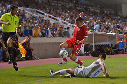 Nicosia, Cyprus - Saturday, October 13, 2007: Wales' captain Craig Bellamy is tackled by Stelios Okkarides before crashing into the assistant referee during the Group D UEFA Euro 2008 Qualifying match against Cyprus at the New GSP Stadium in Nicosia. (Photo by David Rawcliffe/Propaganda)