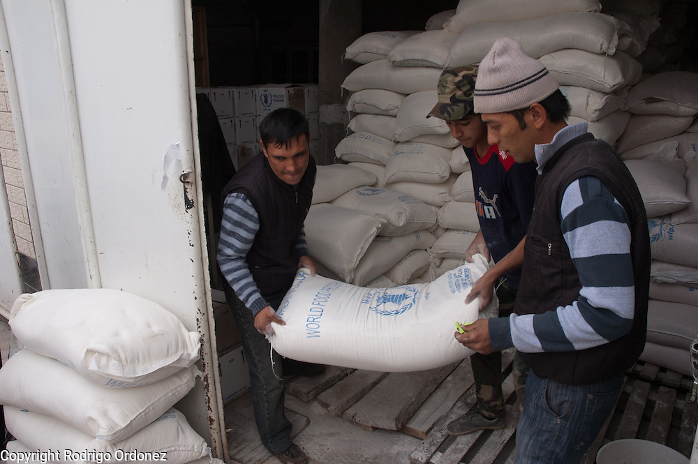 Save the Children staff take sacks out of the warehouse during a distribution of food donated by the World Food Programme (WFP) in the neighborhood of Kizil Kishtak in Osh, Kyrgyzstan.