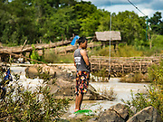 17 JUNE 2016 - DON KHONE, CHAMPASAK, LAOS:  A fisherman looks at the Mekong River near Khon Pa Soi Waterfalls, on the east side of Don Khon. It's the smaller of the two waterfalls in Don Khon. Fishermen have constructed an elaborate system of rope bridges over the falls they use to get to the fish traps they set. Fishermen in the area are contending with lower yields and smaller fish, threatening their way of life. The Mekong River is one of the most biodiverse and productive rivers on Earth. It is a global hotspot for freshwater fishes: over 1,000 species have been recorded there, second only to the Amazon. The Mekong River is also the most productive inland fishery in the world. The total harvest of fish from the Mekong is approximately 2.5 million metric tons per year. By some estimates the harvest in the Tonle Sap (in Cambodia) had doubled from 1940 to 1995, but the number of people fishing the in the lake has quadrupled, so the harvest per person is cut in half. There is evidence of over fishing in the Mekong - populations of large fish have shrunk and fishermen are bringing in smaller and smaller fish.        PHOTO BY JACK KURTZ