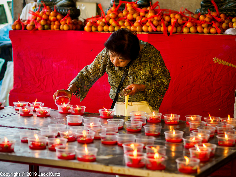 29 JANUARY 2019 - BANGKOK, THAILAND:       A woman lights New Years prayer candles at Wat Mangon Kamalawat, a large Chinese Buddhist temple in Bangkok's Chinatown district. Chinese New Year celebrations in Bangkok start on February 4, 2019. The coming year will be the Year of the Pig in the Chinese zodiac. About 14% of Thais are of Chinese ancestry and Lunar New Year, also called Chinese New Year or Tet is widely celebrated in Chinese communities in Thailand.   PHOTO BY JACK KURTZ