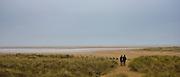 Walkers stroll in wintertime at Holkham beach, North Norfolk, UK
