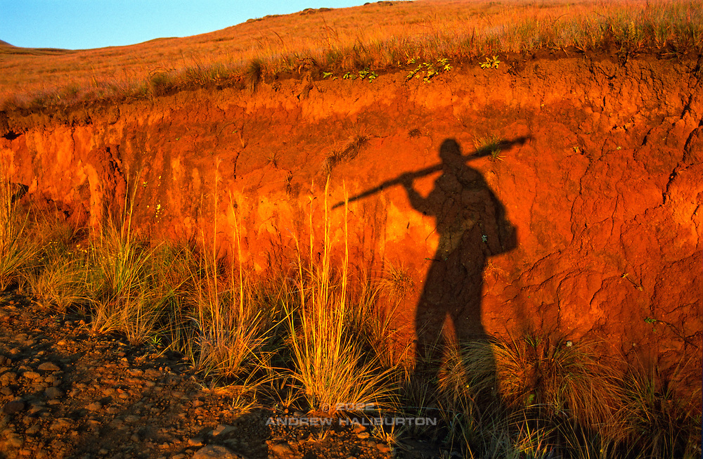 Photographer's shadow, sunrise Mike's Pass. Weathered basalt decomposes to form red clays. Ukhahlamba-Drakensberg Park, KwaZulu-Natal, South Africa.  Nikon F100, 24-50/3.3-4.5D. RVP. April 2004.