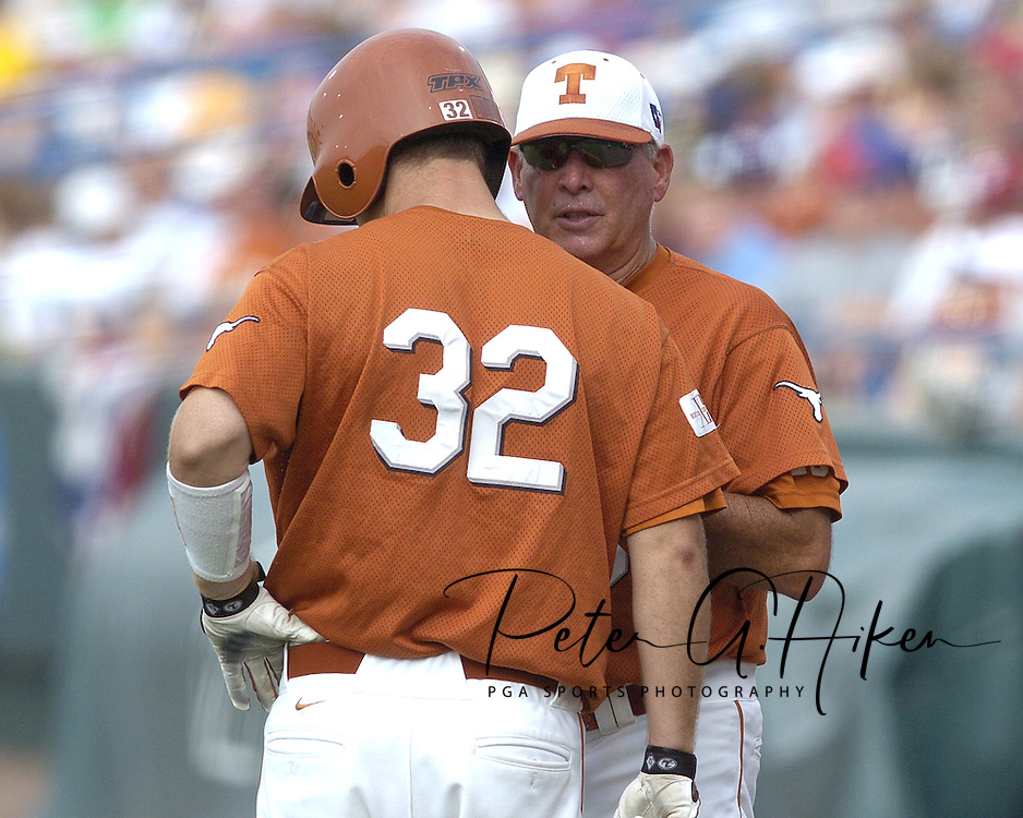 Texas head coach Augie Garrido (R) has a word with Longhorn Carson Kainer (32), before his at bat in the top of the first inning against Florida.  Texas defeated Florida 4-2 in game one of the Championship Series of the College World Series at Rosenblatt Stadium in Omaha, Nebraska on June 25, 2005.