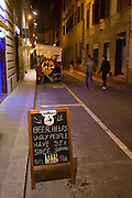 A homemade blackboard urging tourists to enter an Irish Bar stands in the road of a Florence side-street. Apparently beer and alcohol helps ugly people have sex and has done so since Neolithic times. A rough illustration of bottles line the bottom of the writing and in the background we see young men walking away into the distance. It is evening and customers are eating in an outdoor restaurant tent as the blue glow from the bar spreads onto the pavement.