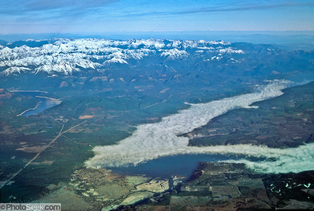 View Skokomish River Delta, fog-filled Hood Canal (part of of Puget Sound and the Salish Sea), the snow-dusted Olympic Mountains, and Lake Cushman from a jet over Washington, USA.