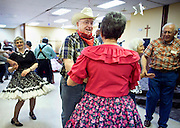 """Al Waskowiak, in hat, square dances with others during a """"Classic Cowboy"""" themed senior citizens prom Thursday afternoon at the Grand Generation Center in Grand Island. (Independent/Matt Dixon)"""