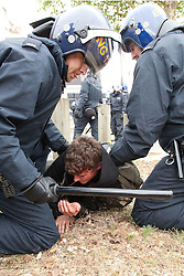 © Licensed to London News Pictures. 14/07/2012. Bristol , UK . Police with batons attempt to lift a man with a head injury off the ground . Anti fascist protesters clash with police as they attempt to block the route for EDL supporters to leave their demontration . The English Defence League hold a march and demonstration in Bristol . Photo credit : Joel Goodman/LNP