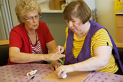 Woman Day Service Officer working with a service user with learning disabilities in an arts and crafts session,