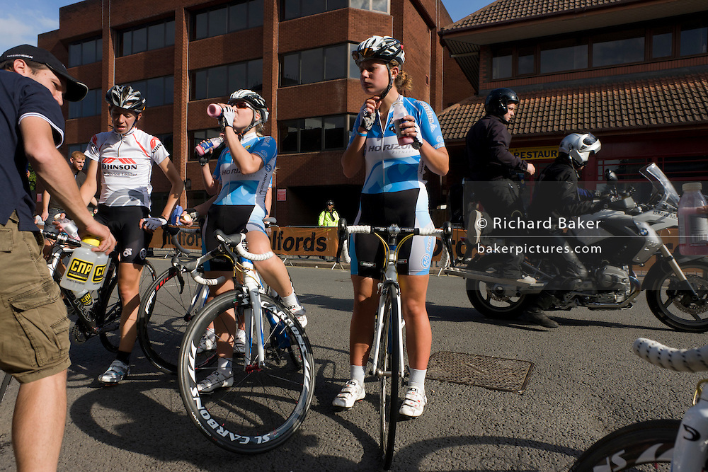 Members of the Horizon Fitness womens' road racing cycling team relax after the competition in Woking streets.