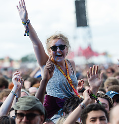© Licensed to London News Pictures. 28/08/2015. Reading Festival, UK.  A female festival goer at Reading Festival dances on her friends shoulders as Palma Violets perform on the main stage on Day 1 of the festival Photo credit: Richard Isaac/LNP