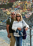 Couple poses for a snapshot while traveling, in Riomaggiore, Cinque Terre, Italy.