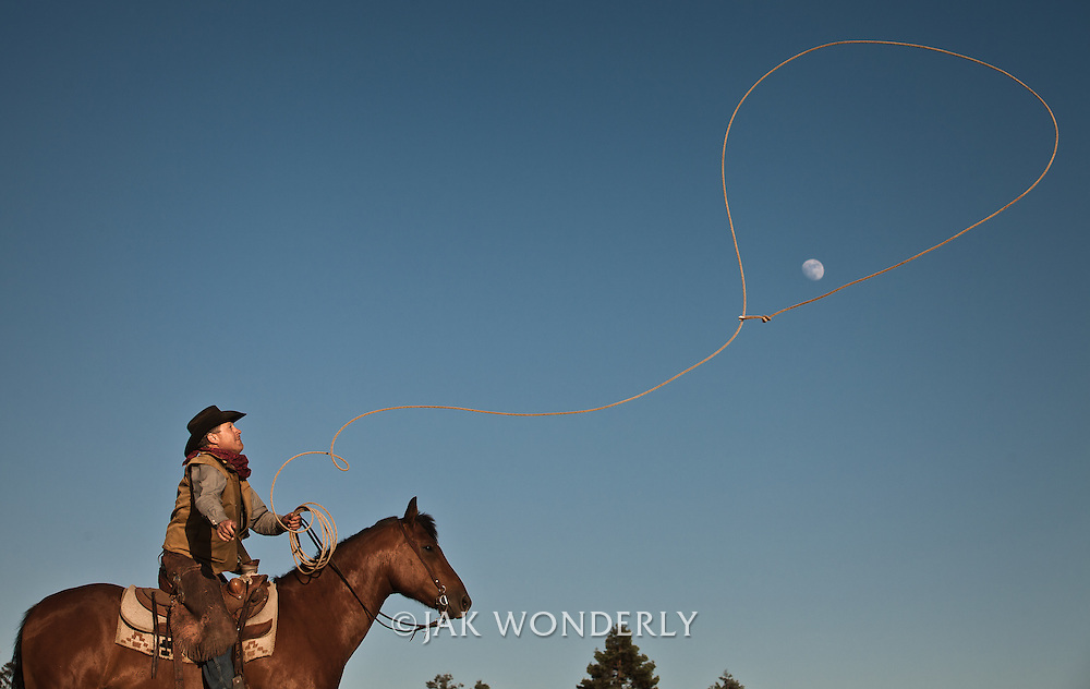 Cowboy on horseback at sunset throws lasso in attempt to grab the moon. Petaluma, California, USA.<br />