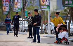 NANNING, CHINA - Wednesday, March 21, 2018: Locals take photographs as the Wales players a team walk near the Wanda Realm Resort ahead of the 2018 Gree China Cup International Football Championship. (Pic by David Rawcliffe/Propaganda)