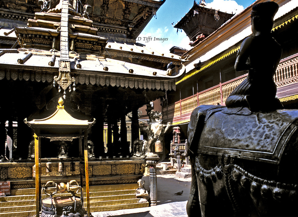Kathmandu, Patan, Golden Temple during Dasain holiday, 2001.  Facade of temple in courtyard; monks' dorms beyond; statue of god seated on elephant faces the facade; rattle symbol on steps of entrance...Temple also called Hiranya Karna Mahabinar, the Kwa Bahal, or the Suvarna Mahavihara, is a unique Buddhist monastery..Kathmandu, Patan, Golden Temple during Dasain holiday, 2001.  Facade of temple in courtyard; monks' dorms beyond; statue of god seated on elephant faces the facade; rattle symbol on steps of entrance...