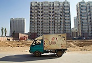 A driver takes a nap while delivering a Chinese version of French bread in the new city of Linhe.