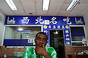 1 August 2007 - Guangzhou, China - Assiongbon Kankoe, 28, from Ghana sits in a Chinese Muslim restaurant. By some estimates over 10,000 Africans from many different nations live and pass through Guangzhou which has overtaken Hong Kong as the new hub for African businessmen looking to cut out the middle man. Some come for a few weeks, others years. These African traders, most of whom come from West African nations like Ghana, Togo and Nigeria, profit by purchasing cheap goods direct from Chinese factories and then sending them back to their home countries where they can be sold at higher prices. Photo Credit: Luke Duggleby