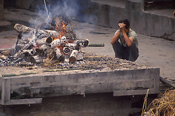 KATHMANDU, NEPAL- A lone mourner pays his last respects as the funeral pyre turns to ash at The Pashupatinath Temple, on the banks of the Baghmati River. This is the holiest Hindu Temple in Nepal. It is here that the faithful come to die and be cremated so that they may attain salvation.(PHOTO © JOCK FISTICK)
