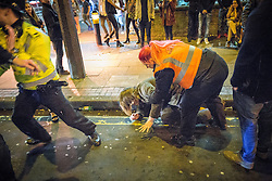 "© Licensed to London News Pictures . 19/12/2015 . Manchester , UK . A taxi marshal helps a man after he was punched , at Deansgate Locks . Revellers in Manchester enjoy "" Mad Friday "" - also known as "" Black Eye Friday "" - the day on which emergency services in Britain are typically at their busiest , as people head out for parties and drinks to celebrate Christmas . Photo credit : Joel Goodman/LNP"