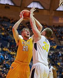 Nov 24, 2018; Morgantown, WV, USA; Valparaiso Crusaders center Derrik Smits (21) shoots while defended by West Virginia Mountaineers forward Logan Routt (31) during the first half at WVU Coliseum. Mandatory Credit: Ben Queen-USA TODAY Sports