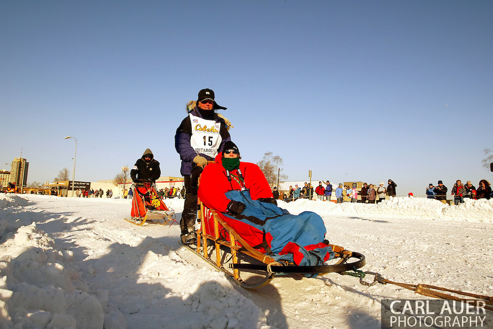 3/3/2007:  Anchorage Alaska -  Most mushers trail a spare sled to keep their dogs from going to fast, as seen here with the sleds of Veteran Ben Stamm of Argyle, WI.  A team hand helps to control the sled and a lucky fan gets to ride in the sled in front of Stamm as well as all the other mushers during the Ceremonial Start of the 35th Iditarod Sled Dog Race