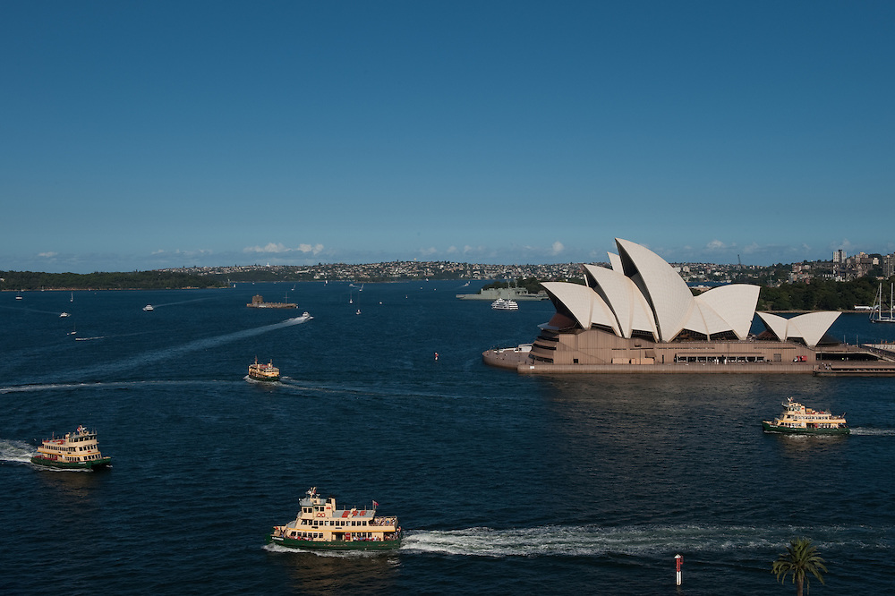 Views of Sydney Harbour and the Sydney Opera House from the Sydney Harbour Bridge, Australia. Sydney Ferries and private yachts crisscross the harbour.
