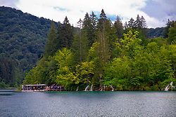 A boat loading tourists, Kozjak Lake, Plitvice Lakes National Park, Croatia. A UNESCO World Heritage site, this natural wonder contains 16 lakes interconnected by rivers and streams. Known for its verdant foliage, numerous waterfalls, and different colored waters, this popular tourist attraction draws more than one million visitors annually.