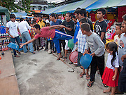 """Sept 29, 2009 - YARANG, THAILAND: Muslim boys play a variation on the carnival ring toss game at a street fair in Yarang, Pattani province, Thailand. Thailand's three southern most provinces; Yala, Pattani and Narathiwat are often called """"restive"""" and a decades long Muslim insurgency has gained traction recently. Nearly 4,000 people have been killed since 2004. The three southern provinces are under emergency control and there are more than 60,000 Thai military, police and paramilitary militia forces trying to keep the peace battling insurgents who favor car bombs and assassination.   Photo by Jack Kurtz / ZUMA  Press"""