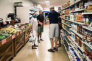 "03 AUGUST 2020 - JEWELL, IOWA:  Shoppers socialize in an aisle in the Jewell Market. The only grocery store in Jewell, a small community in central Iowa, closed in 2019. It served four communities within a 20 mile radius of Jewell. Some of the town's residents created a cooperative to reopen the store. They sold shares to the co-op and  held fundraisers through the spring. Organizers raised about $225,000 and bought the store, which had its ""soft opening"" July 8. The store celebrated its official reopening Monday August 3. Before the reopening, Jewell had been a ""food desert"" for seven months. The USDA defines rural food deserts as having at least 500 people in a census tract living 10 miles from a large grocery store or supermarket. There is a convenience store in Jewell, but it sells mostly heavily processed, unhealthy snack foods that are high in fat, sugar, and salt.          PHOTO BY JACK KURTZ"