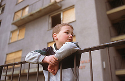 Young boy leaning over railings outside derelict and boarded up block of flats in Radford Nottingham,