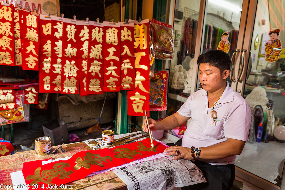 31 JANUARY 2014 - BANGKOK, THAILAND:   A calligrapher works on backstreet during Lunar New Year festivities, also know as Tet and Chinese New Year, in Bangkok. This year is the Year of the Horse. Ethnic Chinese make up about 14% of Thailand and Chinese holidays are widely celebrated in Thailand.     PHOTO BY JACK KURTZ