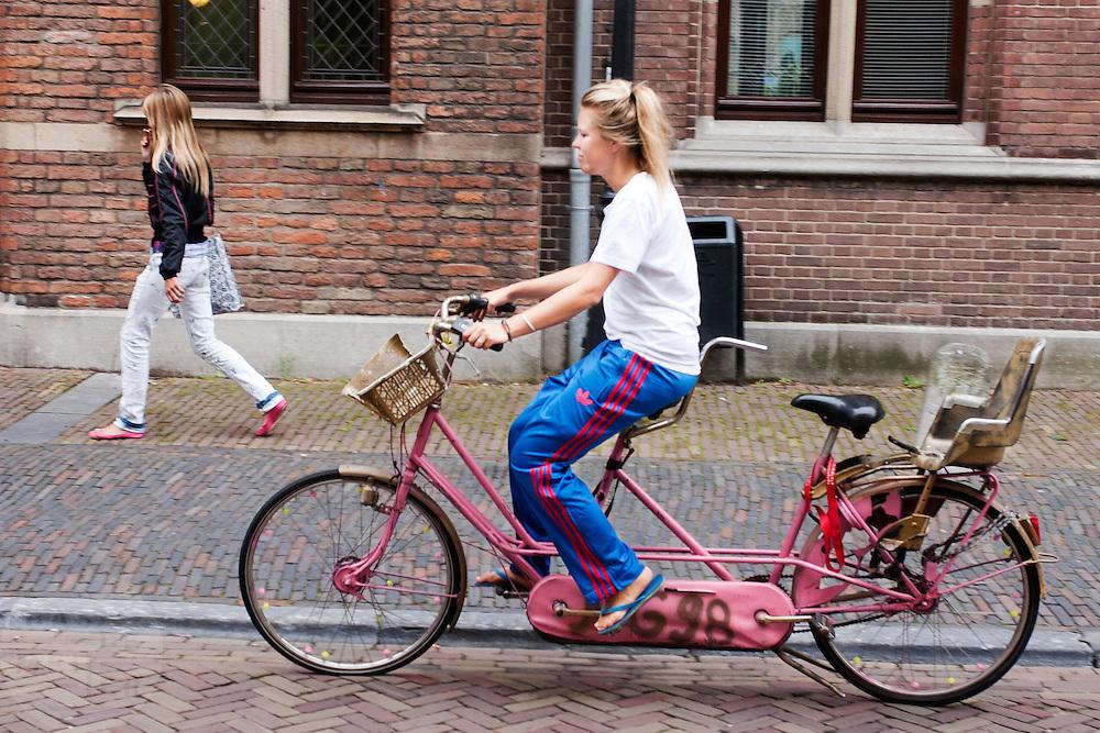 Een vrouw fietst alleen op een tandem door het centrum van Utrecht.<br /> <br /> A woman is cycling on a tandem in Utrecht